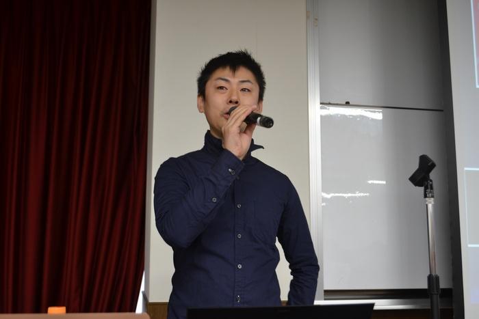 WordCamp大阪2012のスピーカーである松尾茂起氏がマイクを持って講演している画像